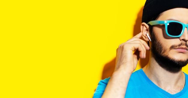무선 이어폰 / 이어 버드를 사용하여 손가락으로 만지는 젊은 소식통의 클로즈업. 청록색, 파란색 셔츠, 검은 색 비니 모자를 쓰고 있습니다. 복사 공간 노란색의 스튜디오 배경입니다.