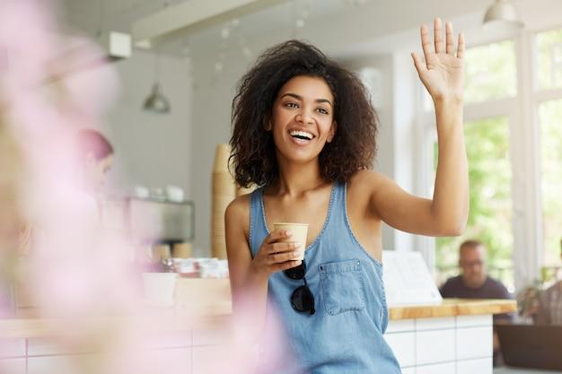 カフェテリアに座って、コーヒーを飲んで、幸せで興奮した表情で友達を振ってカジュアルな青いシャツを着て黒い巻き毛のうれしそうな浅黒い若い学生女性のクローズアップ。