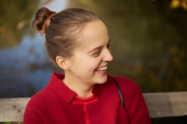 Крупным планом молодая леди эмоционально смеется, сидя на открытом воздухе на берегу реки