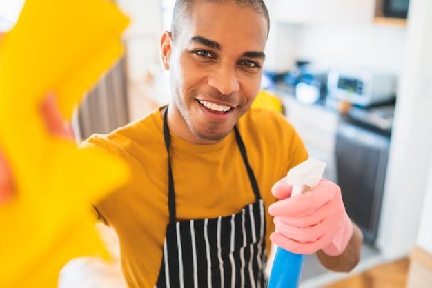 新しい家で掃除をしている若いラテン系男性のクローズアップ。ハウスキーピングとクリーニングのコンセプト。