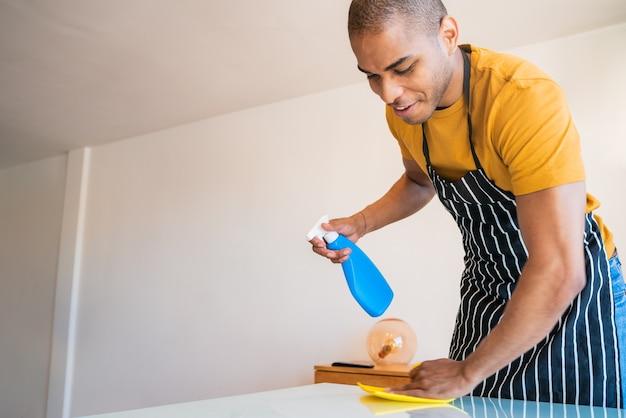 自宅のテーブルから汚れを掃除している若いラテン系男性のクローズアップ。ハウスキーピングとクリーニングのコンセプト。