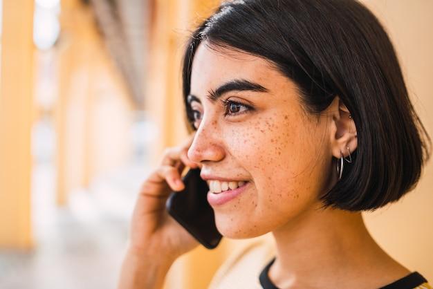 通りで屋外の電話で話している若いラテン女性のクローズアップ。都市のコンセプト。
