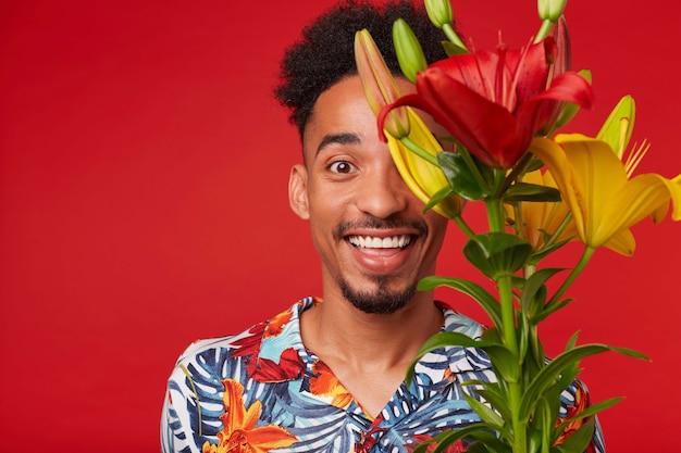 Крупным планом молодой смеющийся афроамериканец в гавайской рубашке, смотрит в камеру с счастливым выражением лица, держит букет желтых и красных цветов, стоит на красном фоне.