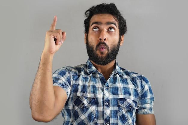 Крупным планом молодой мужчина показывает что-то в верхней части, используя руку руку
