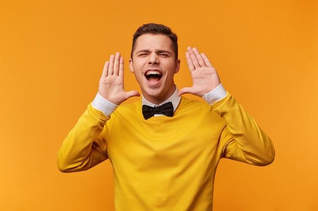 Крупным планом молодой человек добился успеха, удача ему улыбнулась, изображает победный танец, подняв руки вверх