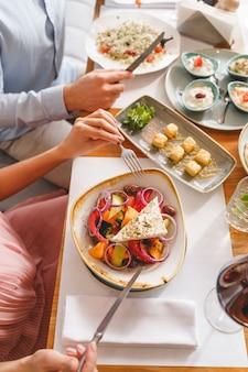 신선한 샐러드와 소스를 곁들인 테이블에 앉아 있는 젊은 남녀의 클로즈업