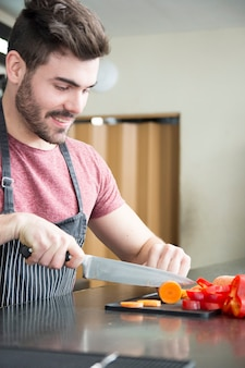 Close-up of young man cutting slices of carrot with sharp knife