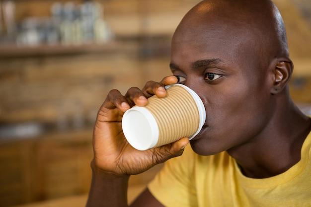 Крупный план молодого человека, пьющего кофе из одноразовой чашки в кафе