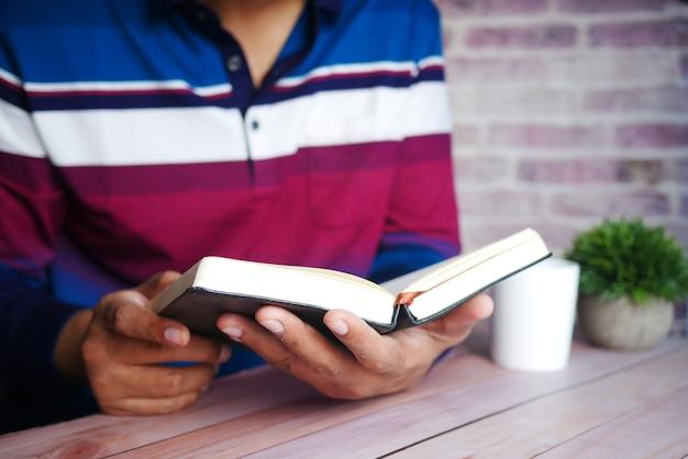 책을 읽는 젊은 남자 손 클로즈업