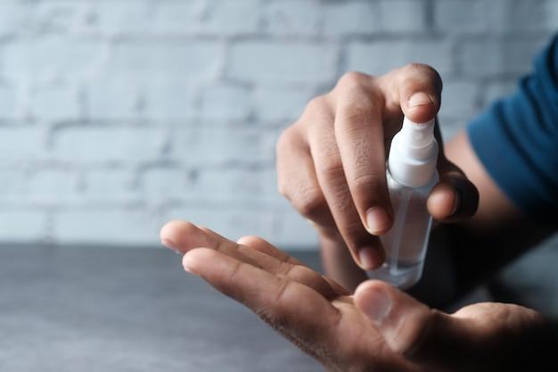 手の消毒剤スプレーを使用して若い男の手のクローズアップ。