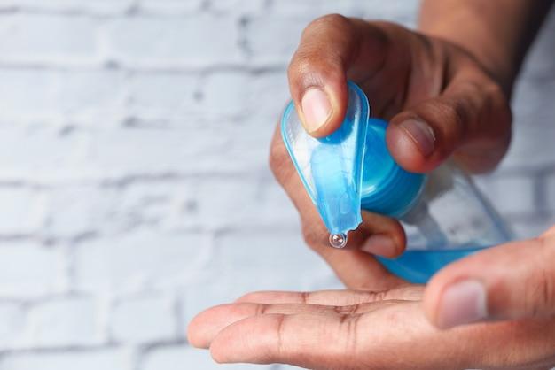 Крупным планом руки молодого человека, использующего дезинфицирующий гель для предотвращения вируса
