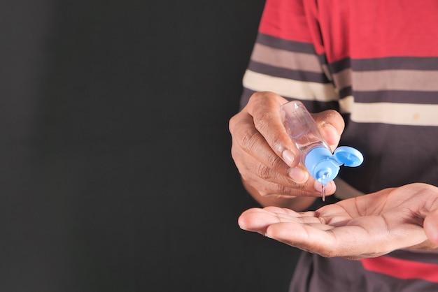 Закройте руки молодого человека, используя дезинфицирующий гель для предотвращения вируса.