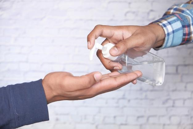 ウイルスを防ぐために消毒ジェルを使用して若い男の手のクローズアップ