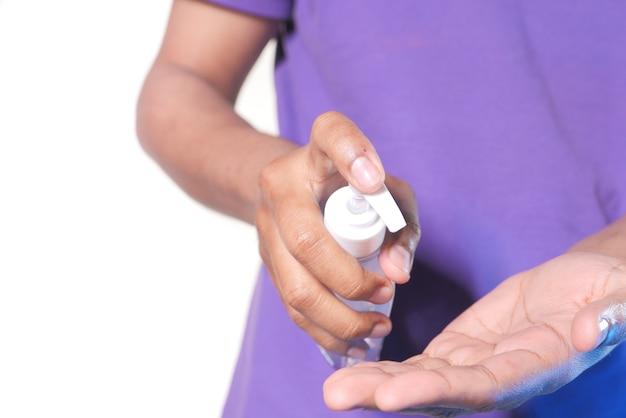 ウイルスを防ぐために消毒ジェルを使用して若い男の手のクローズアップ。