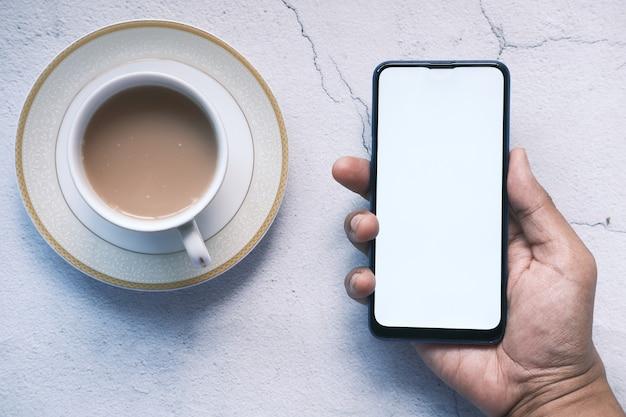 Закройте руки молодого человека, используя смартфон с пустым экраном