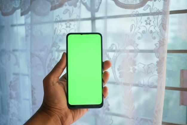 Закройте руки молодого человека, используя смартфон с зеленым экраном