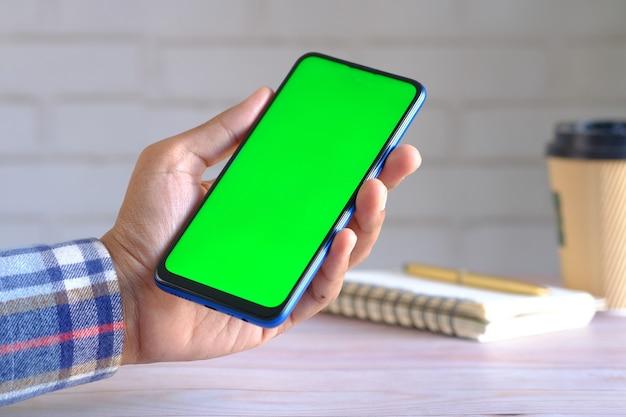 Крупным планом руки молодого человека с помощью смартфона с зеленым экраном