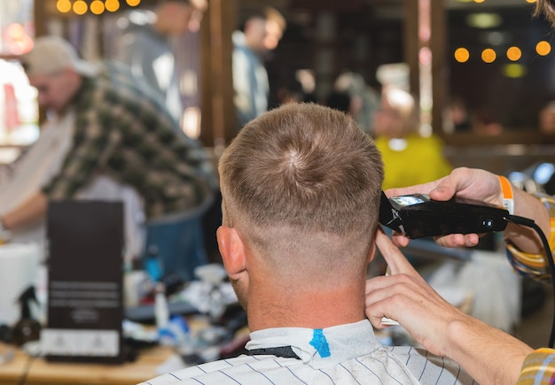 이발소에서 스타일리스트가 면도 한 머리와 머리의 측면을 가진 젊은 남자의 닫습니다