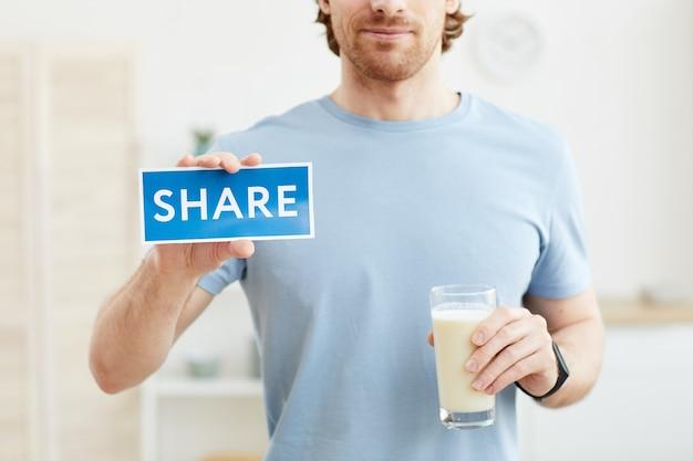Крупным планом молодой человек держит стакан молока и делится своим опытом