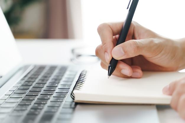 Закройте молодого человека в случайных руках ткани, записывая на блокноте, тетради, используя шариковую ручку с портативным компьютером на столе.