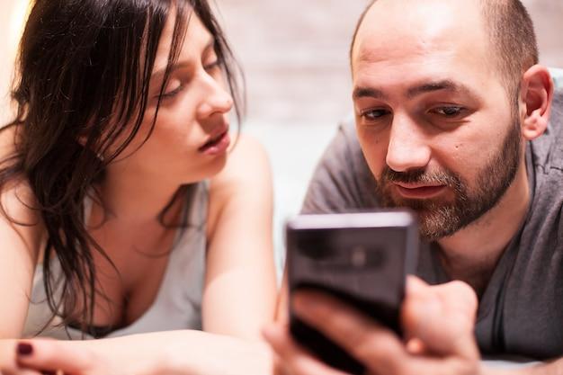 Крупным планом молодой человек в пижаме с помощью смартфона, в то время как его жена смотрит на него.