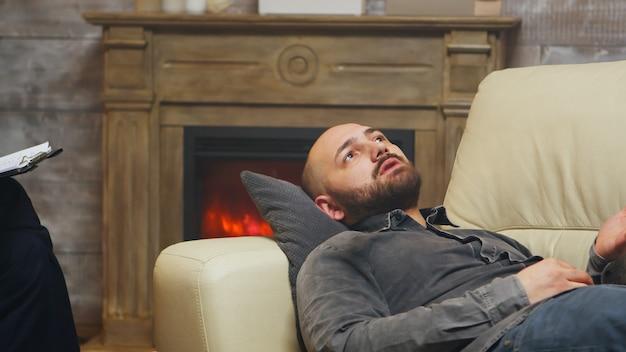 関係カウンセリングでソファに横たわっている若い男のクローズアップ。