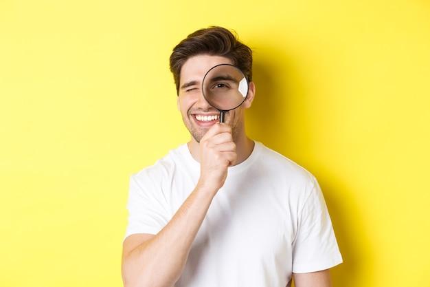虫眼鏡を通して見て、笑顔、何かを探して、黄色の背景の上に立っている若い男のクローズアップ。