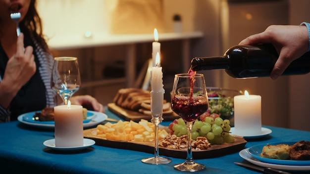 아내 유리에 레드 와인을 붓는 젊은 남자의 닫습니다. 로맨틱한 백인 행복한 커플은 촛불, 사랑, 기념일을 축하하며 부엌 테이블에 앉아 있습니다. 관계에서 로맨스 놀라움