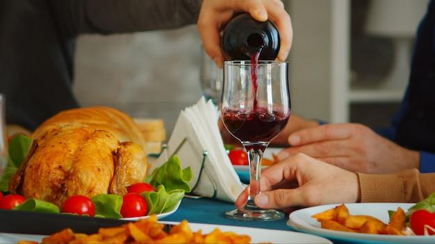 家族の集まりで彼の父に赤ワインを注ぐ若い男のクローズアップ。
