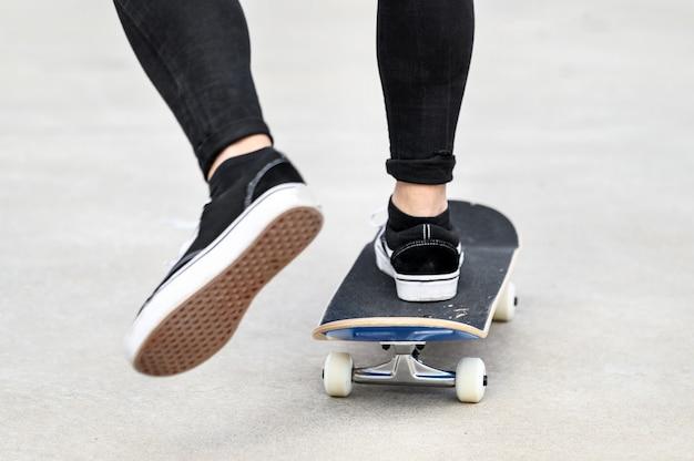 スケート公園でスケートボードに乗って若い男のクローズアップ。
