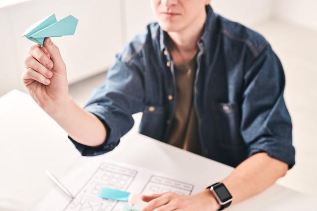 Крупный план молодого человека, сидящего за столом и бросающего бумажный самолетик, работая над дизайном пользовательского интерфейса в офисе