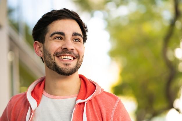 Крупным планом молодой человек улыбается, стоя на улице на улице