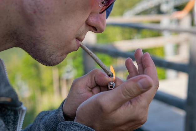 젊은 남자 흡연 마리화나 합동 야외의 클로즈업.