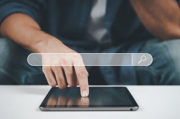 ソファでタブレットを使用して若い男のクローズアップ。検索、ブラウジング、オンラインショッピング、ソーシャルネットワーク。