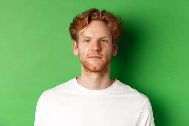 Крупный план молодого человека с рыжими растрепанными волосами и бородой, смотрящего в камеру, стоящего на зеленом фоне