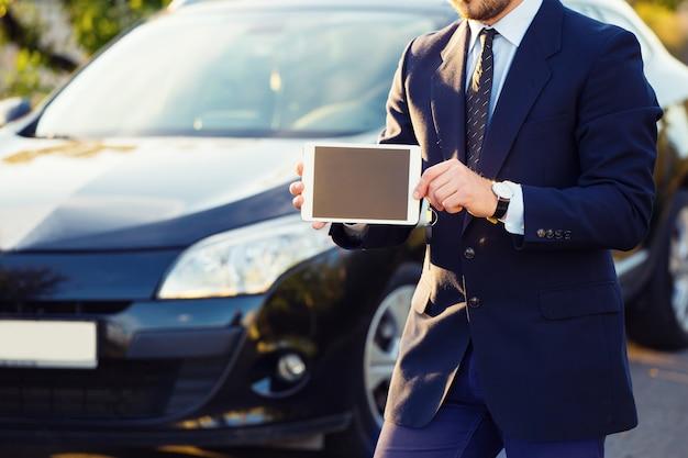 タブレットpcコンピューターと車の屋外で若い男のクローズアップ