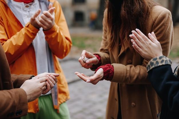 屋外の手に消毒剤をスプレーする若い男性と女性のクローズアップ。ウイルスから保護するための抗菌剤。