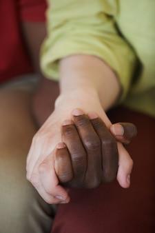 手をつないで若い多民族カップルのクローズアップ