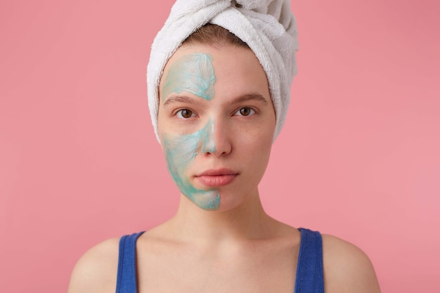 샤워 후 그녀의 머리에 수건으로 멋진 아가씨를 닫고, 효과를 비교하기 위해 바닥에 마스크를 씌우고, 스탠드를 보입니다.