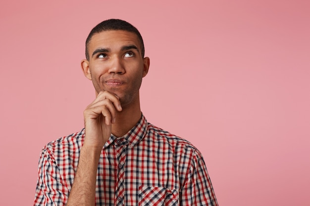 市松模様のシャツを着た若い物思いにふける魅力的な暗い肌の男のクローズアップは、目をそらしてあごに触れ、考えて疑い、右側にコピースペースがあるピンクの背景の上に立っています。