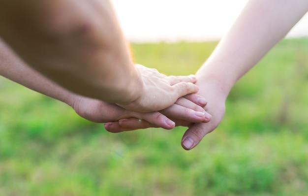 그들의 손을 함께 넣어 젊은 사람들의 클로즈업입니다. 손을 잡고 있는 친구는 연대와 팀워크를 보여줍니다.