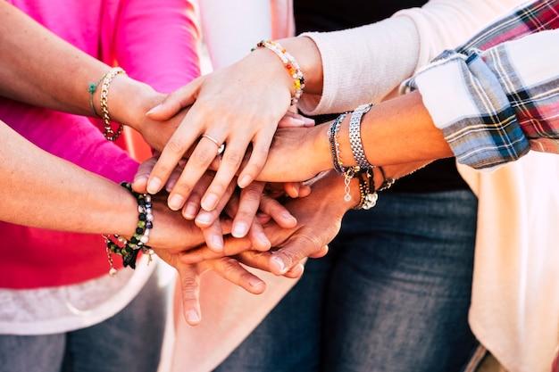 手を合わせている若者のクローズアップ。団結とチームワークを示す手のスタックを持つ友人。ワイストとフリンジャーのアクセサリーで女性の手のクローズアップ。