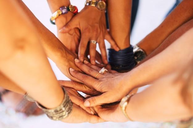 手を合わせている若者のクローズアップ。団結とチームワークを示す手のスタックを持つ友人。多様性の人々のグループが一緒にサポートを積み重ねます