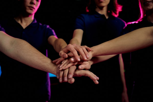 ゲームに勝つために団結しながら手を積み重ねる若者のクローズアップ