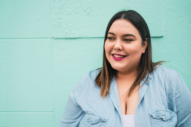 야외에서 밝은 파란색 벽에 서있는 동안 웃 고 젊은 더하기 크기 여자의 클로즈업.