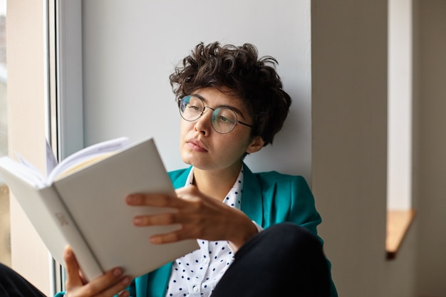 手に本を持って、窓辺に座って、集中した顔で中を見る眼鏡の若いかなり茶色の目の短い髪の巻き毛の女性のクローズアップ