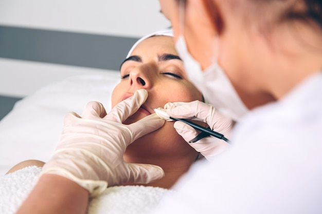 Закройте молодой красивой женщины, получающей лечение rf подъема в клиническом центре. концепция медицины, здравоохранения и красоты.