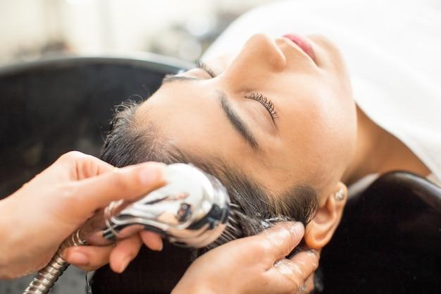 Крупный план молодой расслабленной женщины в парикмахерской