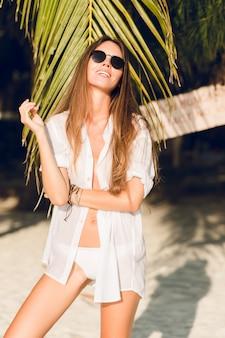 그린 팜 리프와 흰색 비키니 수영복을 입고 해변에 서있는 젊은 섹시 슬림 여자의 클로즈업. 그녀는 흰색 셔츠에 검은 색 선글라스를 착용합니다. 그녀는 무두질하고 세련된