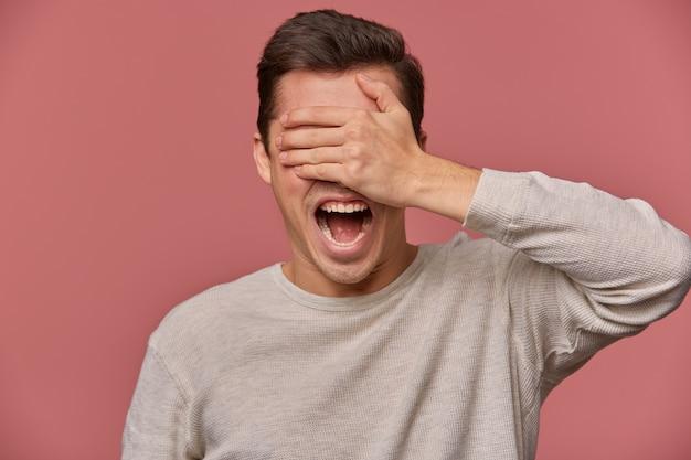 Крупным планом молодой шокированный парень в пустом длинном рукаве, стоит на розовом фоне с широко открытыми глазами и кричит, прикрывает глаза ладонью.